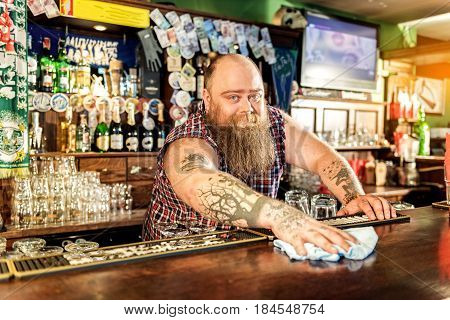 Portrait of bearded man demonstrating joy while wiping counter in beerhouse