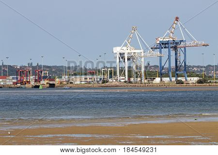 DURBAN SOUTH AFRICA - APRIL 9 2017: Early morning low tide container ship and loading cranes in harbor in Durban South Africa