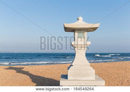 Stone lantern and sand beach