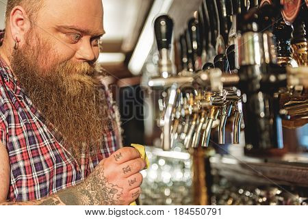 It is so shine. Bearded male bartender expressing happiness while washing beer tap in boozer