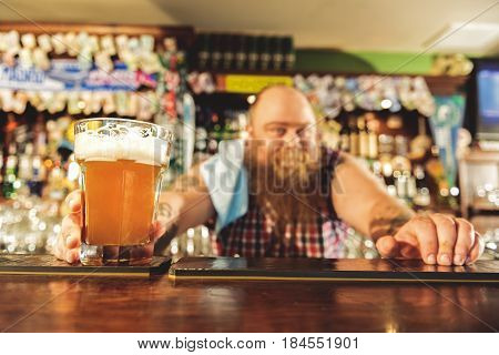 Focus on male hand giving glass of beer on table. He working in pub
