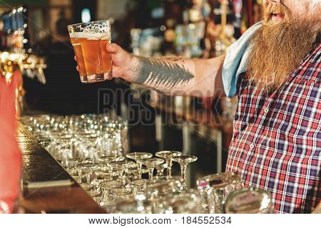 It is most delicious alcohol beverage. Focus on hand of happy bearded man showing cup of alcohol in boozer