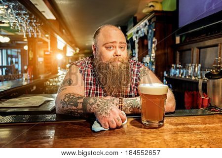Fat male bartender expressing thoughtfulness while leaning on workplace in pub