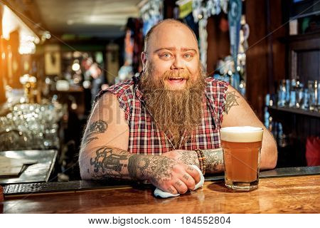 Portrait of fat man showing happiness while standing at counter in tap-room