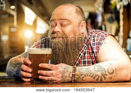 This sweet smell of fresh alcohol. Fat man showing enjoyment while tasting cold foamy ale in tap-room
