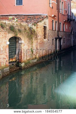 canal in venice wih reflections of buildings old walls doors and windows