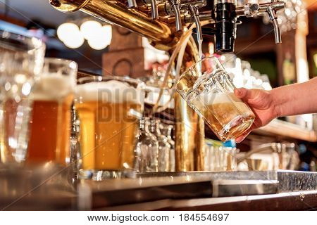 Focus on low angle of close up male arm pouring beer in alehouse