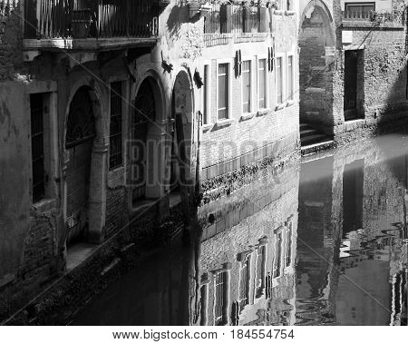 canal in venice with reflections of buildings old walls doors and windows