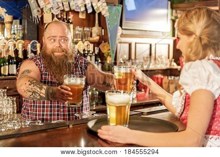 Here is delicious beverage for our clients. Bearded man expressing cheerfulness while giving drinks to waitress in pub
