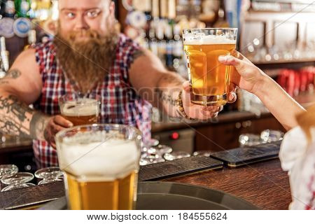 Focus on alcohol beverage which keeping fat male in pub