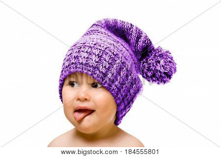 Happy child in hat smiling, sticking his tongue out, isolated over white