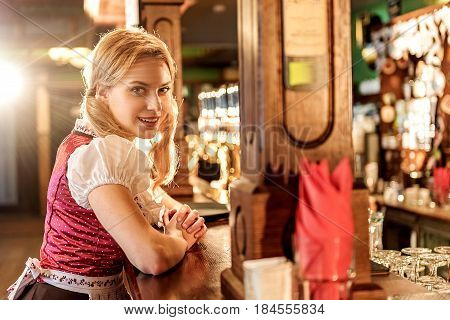 Waitress showing happiness while leaning on surface of counter in pub