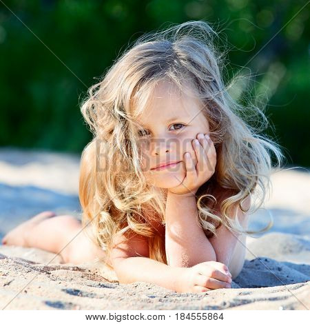 Cute baby girl lying on sand, summer time