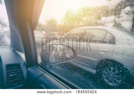 Car Drive In Raining Season. Vehicle Side Windows With Rain Drops Water And Sun Background.