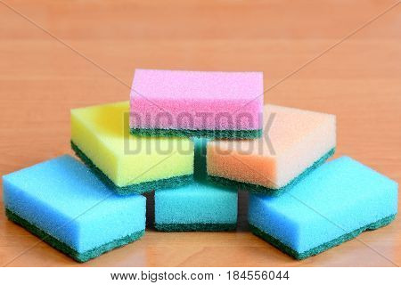 Colorful sponge for cleaning ware and house cleaning. Cleaning sponge with scrub set isolated on a wooden table. Closeup