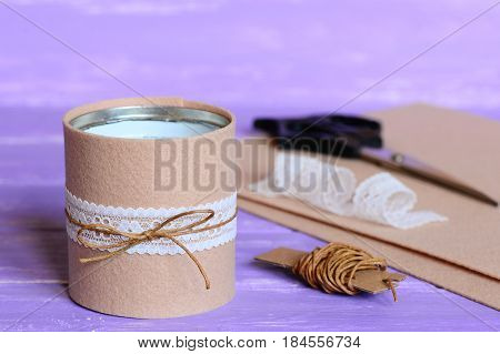 Recycling tin cans into organizer to contain pens, pencils, markers and other office supplies. Easy recycled craft idea. Materials and tools for art work on a wooden table. Closeup