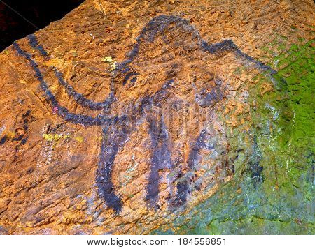 Prehistoric Art Of Mammoth In Sandstone Cave. Spotlight Shines On Historical Painting