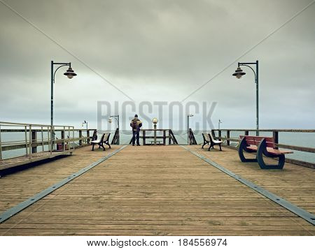 Man On Wooden Mole In Harbor Within Autumn Misty Day. Tourist At Handrail.