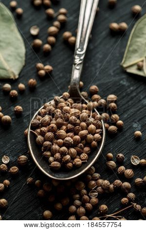 Coriander Dry Seeds In Metal Spoon On A Black Wooden Table, Vertical