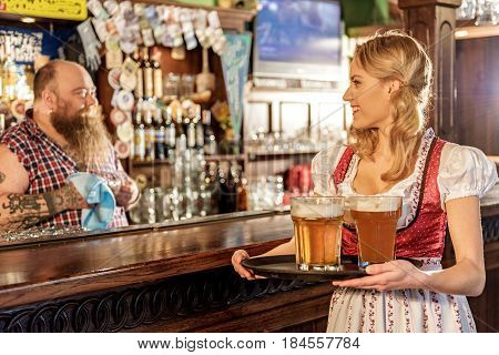 Side view of waitress showing gladness while telling with bearded bartender in pub
