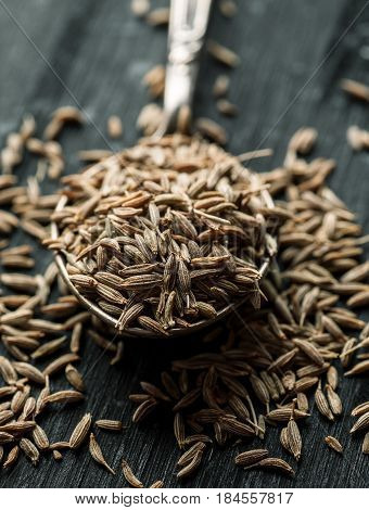 Cumin Dry Seeds In Metal Spoon On A Black Wooden Table, Macro Shot