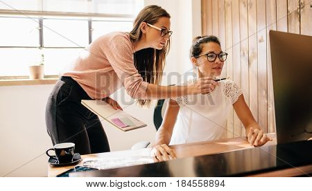 Creative business women working on desktop computer together in office. Two female coworkers working and looking at computer monitor.