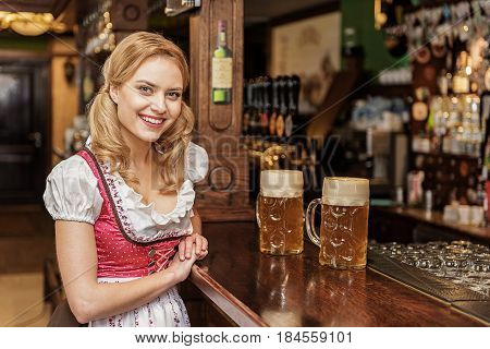 Portrait of woman demonstrating happiness while leaning on counter in dramshop . She looking at camera