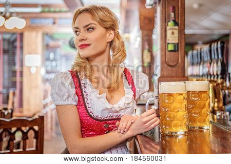 Woman demonstrating dreaminess while looking away. She standing near counter with alcohol on it n boozer