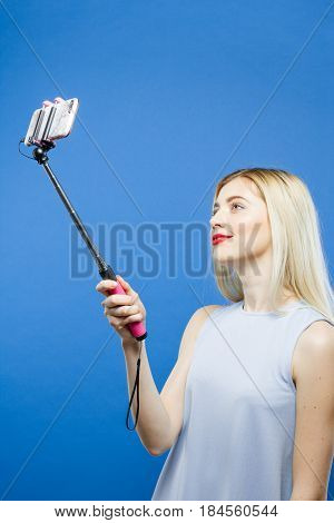 Joyous Blonde Taking Photo Using Selfie Stick on Blue Background. Cute Girl in Dress Photographing Herself by Smartphone in Studio. Vertical.