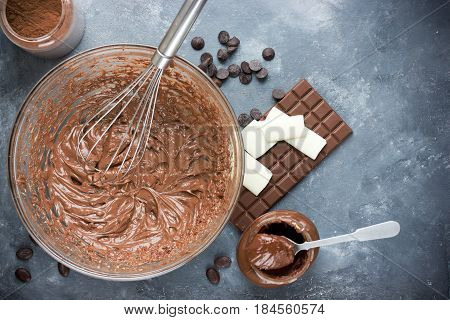 Chocolate cream in bowl and chocolate ingredients on the table top view