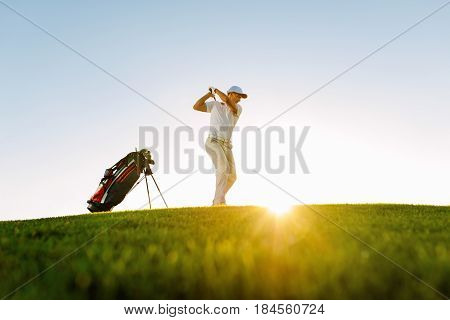Male Golfer Taking Shot On Golf Course