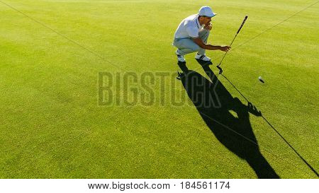 Golfer Checking Line For Putting Golf Ball