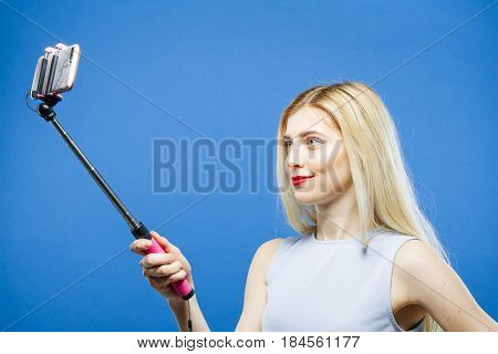Beautiful Young Woman with Long Hair and Red Lips Photographing Herself by Smartphone in Studio. Pretty Blonde is Grimacing While Taking a Photo Using Selfie Stick on Blue Background, Closeup.