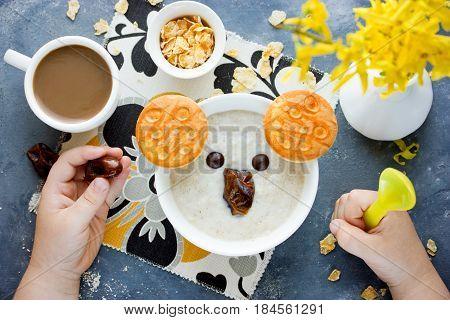 Funny idea for healthy kids breakfast - oat bran porridge bowl in the form of koala face