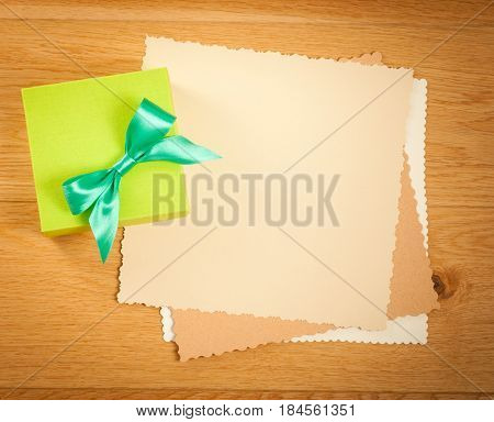 Green gift box with blank gift tag on wooden background