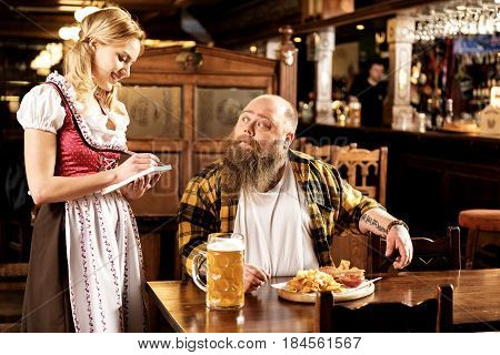 What do you want to eat. Surprised man with overweight telling smiling waitress what food bring him in pub