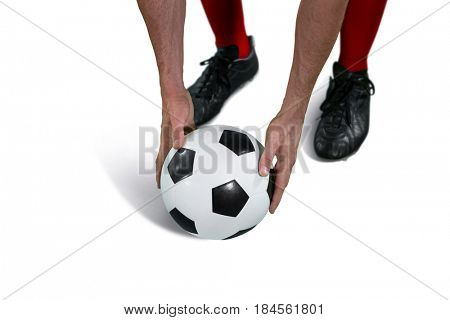 Football player placing football on white background