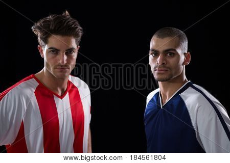 Portrait of two football players standing against black background