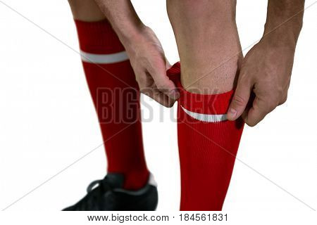 Football player pulling his socks up against white background