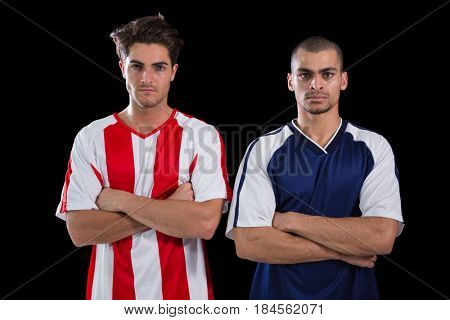 Two football players standing with arms crossed against black background