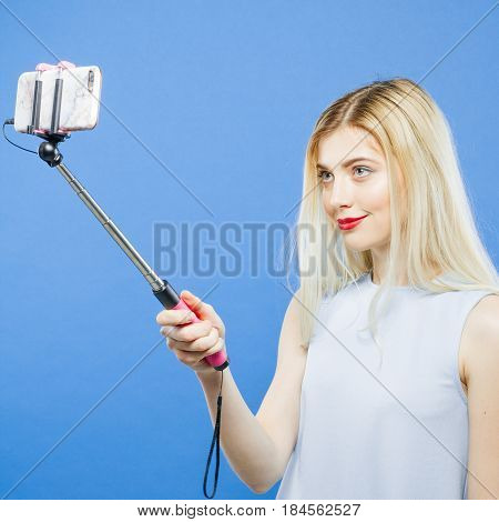 Closeup Portrait of Young Woman with Long Hair and Sensual Red Lips Photographing Herself by Smartphone in Studio. Blonde is Grimacing While Taking a Photo Using Selfie Stick on Blue Background.