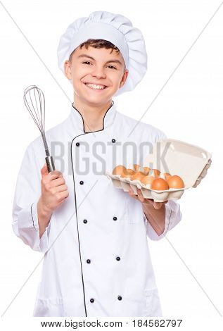 Handsome teen boy wearing chef uniform holding hand mixer or wire whisk. Portrait of a happy cute male child cook with eggs and egg beater, isolated on white background. Food and cooking concept.