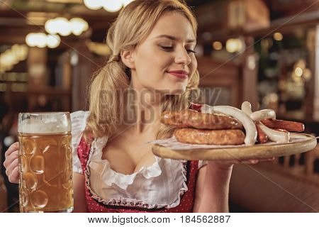 This delicious meal. portrait of cheerful waitress bearing order to table in pub