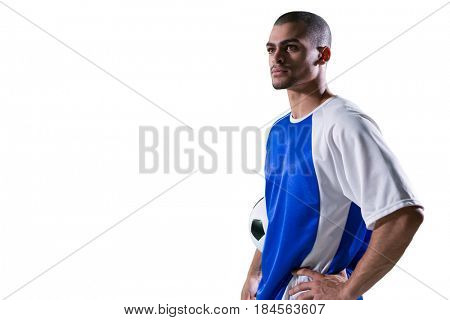 Football player holding football against white background