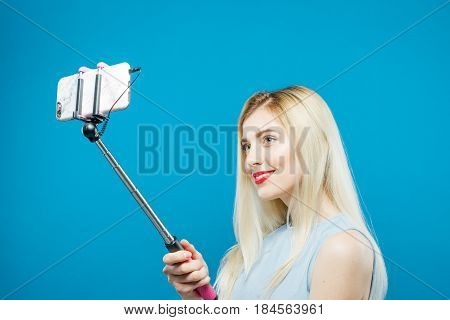 Amazing Blonde with Sensual Lips and Wild Smile Photographing Herself. Smiling Girl Using Selfie Stick to Take a Photo on Blue Background in Studio.