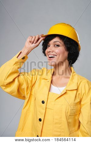 Happy smiling mixed race construction woman wearing yellow protect helmet and overall adjusting helmet, over grey background