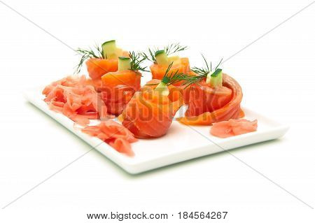 Rolls of salmon with cucumber and dill on a plate. White background - horizontal photo.
