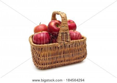Basket with red apples on a white background. Horizontal photo.