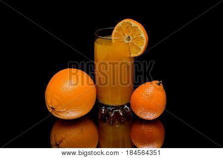 Orange mandarin and glass with juice on a black background. Horizontal photo.