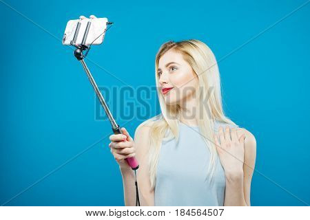 Portrait of Cute Blonde with Sensual Lips Photographing Herself. Smiling Girl Using Selfie Stick to Take a Photo on Blue Background in Studio.